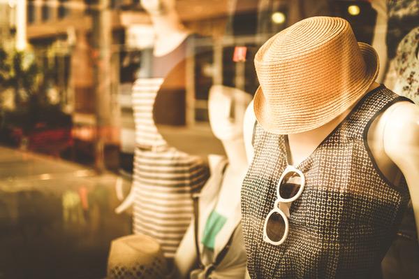 Schaufensterpuppe im Schaufenster, mit Sommerkleid, Sonnenhut und Sonnenbrille