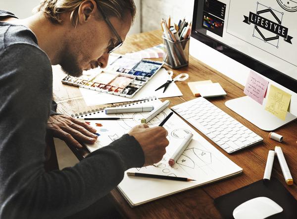 Junger Mann an einem Schreibtisch zeichnet auf einem Block mit Stiften, vor sich ein Computerbildschirm