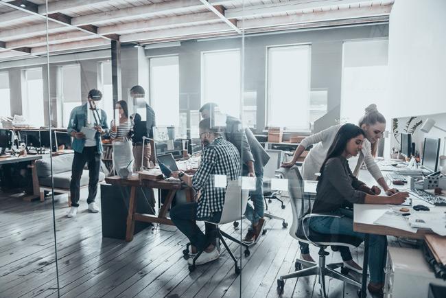 Junge Mitarbeiter in einem Buero hinter Glastueren an Schreibtischen mit Computern, helle Fensterfront