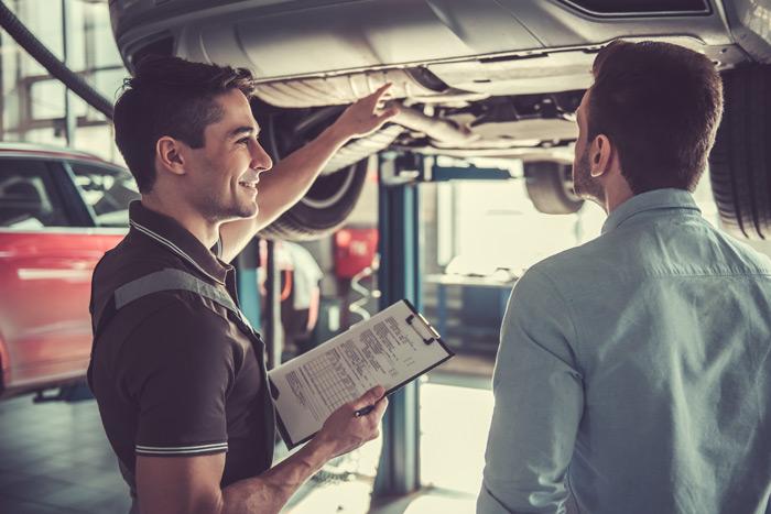 zwei junge Maenner in der Werkstatt an einem Auto auf der Hebebuehne, mit Klemmbrett in der Hand, deutet auf den Unterboden