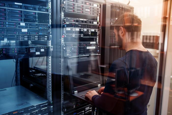 junger Mann an einem Laptop vor einer technischen Anlage mit vielen Knoepfen und Schaltern