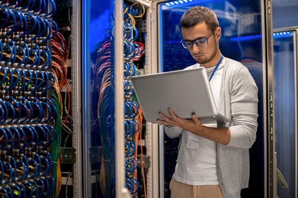 junger Mann mit Brille und Laptop in der Hand vor einem geoeffneten Server-Schrank voller bunter Kabel