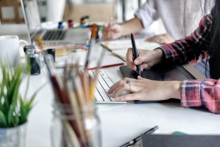 Zwei Personen an einem Bueroschreibtisch, Haende auf Laptoptastaturen, auf dem Tisch Stifte