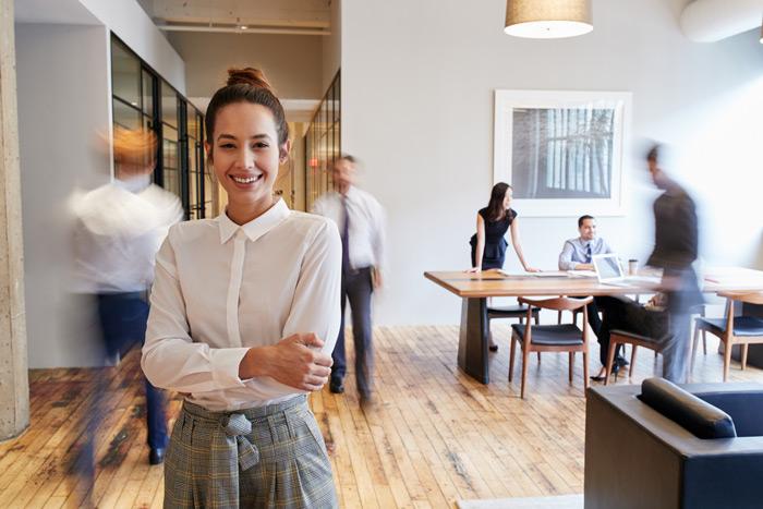 Junge Frau im Business Outfit im Buero laechelt mit verschraenkten Armen, im Hintergrund Kollegen an Tischen und im Flur