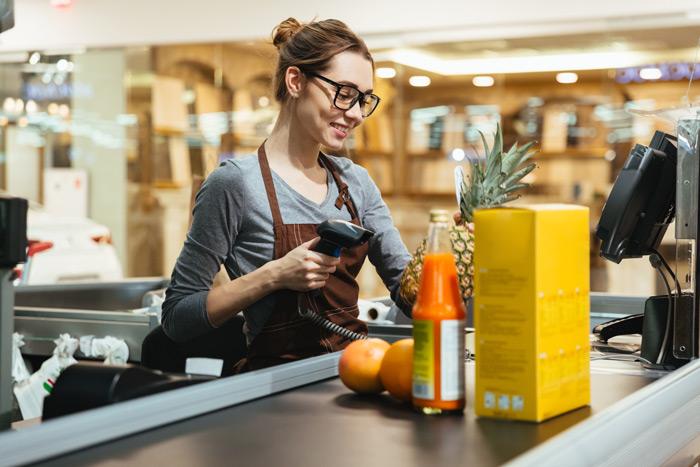 Auszubildende im Einzelhandel an der Supermarktkasse scannt eine Ananas, vor ihr Lebensmittel auf dem Warenband
