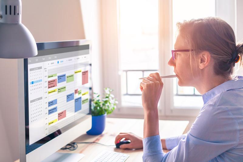 Frau im Buero vor einem Computer-Bildschirm mit einem Stift in der Hand, schaut sich einen digitalen Kalender an