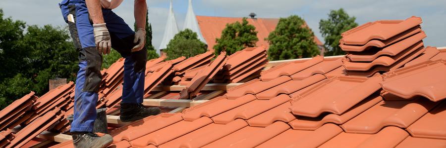 Dachdecker steht in Arbeitskleidung und Arbeitshandschuhen auf einem Dach, neben sich abgedeckte Dachpfannen,