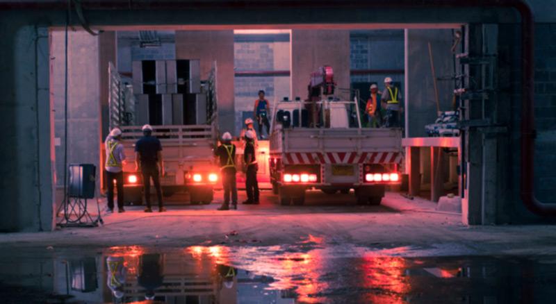 Personen in Arbeitskleidung und Schutzhelmen stehen in einer Lagerhalle neben Arbeitsfahrzeugen