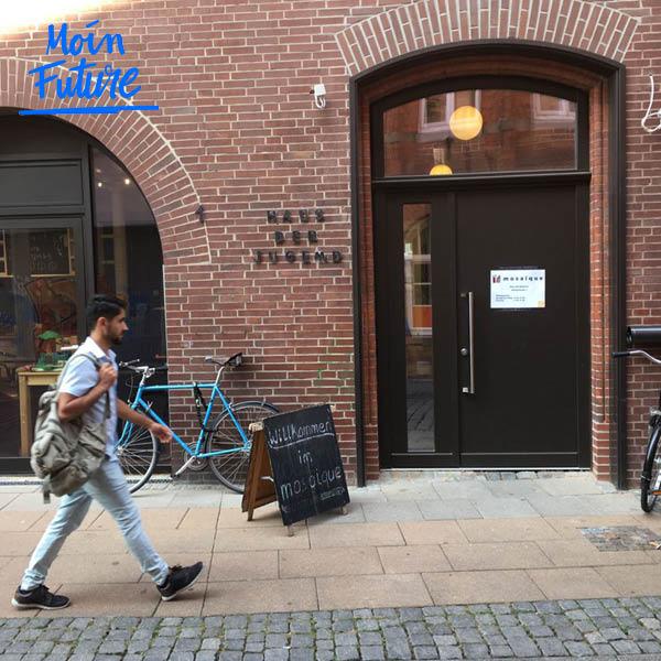 Auszubildender Obaidulah geht ins Mosaique in Lüneburg, an der Wand lehnt ein hellblaues Fahrrad