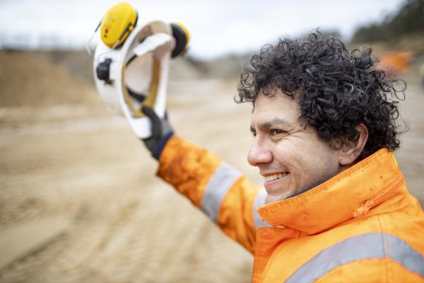 Auszubildender Titos auf der Baustelle in Arbeitskleidung, hält einen Schutzhelm in der Hand