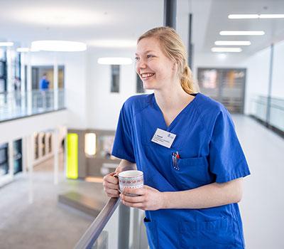 Auszubildende Gesundheits- und Krankenpflegerin im Flur eines Krankenhauses, lehnt am Treppengeländer mit einer Kaffeetasse in der Hand, Ausbildung in der Region, Niedersachsen