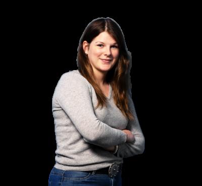 Auszubildende Luisa wird Groß-und Außenhandelskauffrau, verschraenkt die Arme, traegt grauen Pullover und dunkelblaue Jeans