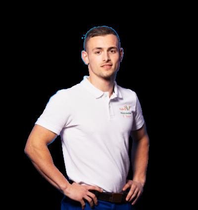 Auszubildender Erwin wird Elektroniker für Energie-und Gebaeudetechnik, hat Hände in den Hueften und laechelt, traegt Schutzkleidung, weißes T-Shirt, dunkelblaue Hose