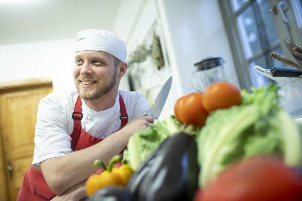 Auszubildender Koch Leonardo in der Kueche mit einem Messer, im Vordergrund Auberginen, Salat, Tomaten, Paprika