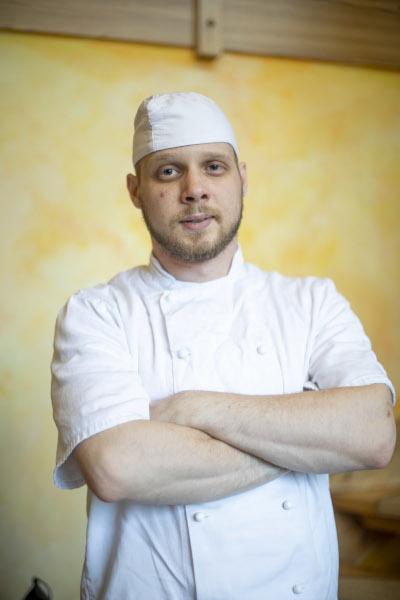 Auszubildender Koch Leonardo schaut in Arbeitskleidung und mit verschraenkten Armen in die Kamera