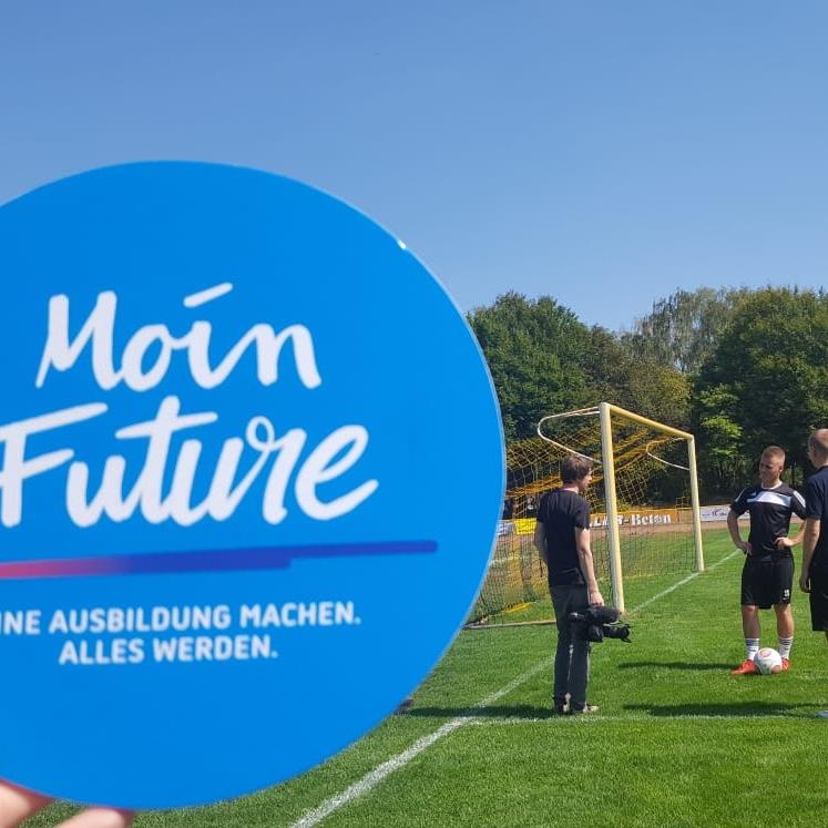 Ein Kamerateam filmt einen jungen Auszubildenden in seiner Freizeit auf dem Fußballplatz, davor das blaue Moin Future-Logo