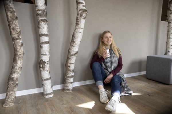 Auszubildende Tourismuskauffrau Karina auf dem Boden sitzend mit einer Kaffeetasse in der Hand