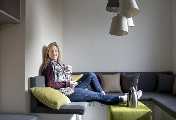 Auszubildende Tourismuskauffrau Karina in einer Sofaecke mit hochgelegten Beinen und Kaffeetasse in der Hand, vor sich auf dem Tisch eine Kafeekanne
