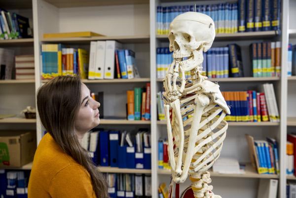 Auszubildende Gesundheits- und Krankenpflegerin Lea neben einem Skelett, vor einem Regal mit Büchern und Akten