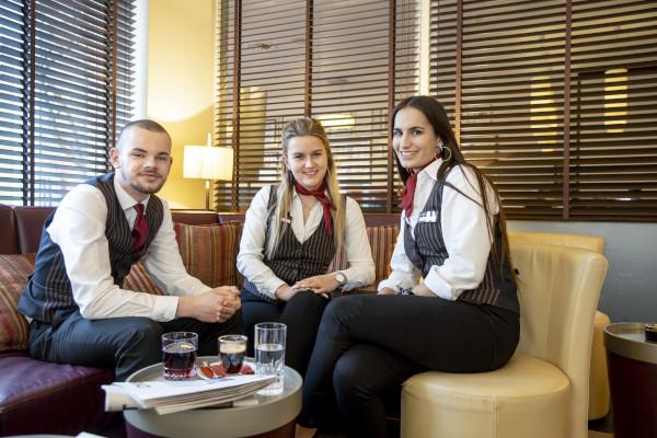 Drei Auszubildende Hotelfachleute in einer Sofaecke, vor sich ein Tisch mit Getraenken