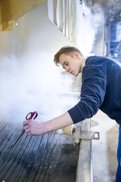 Auszubildender in der Industrie, Felix, an einer dampfenden Industrieanlage