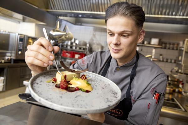Auszubildender Koch in der Küche mit einem Teller in der Hand, kunstvolles Dessert mit Himbeeren, in Arbeitskleidung