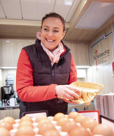 Auszubildende Kauffrau im Einzelhandel lacht mit einem Eierkarton in der Hand, vor sich Eierpappen mit braunen Eiern darin