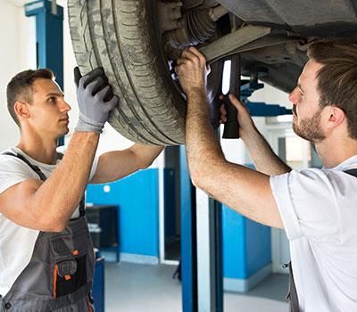 Zwei KFZ Mechaniker in der Werkstatt wechseln einen Reifen, Auto auf der Hebebühne, Ausbildung, Moin Future
