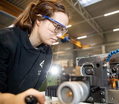 Auszubildende an der Werkbank in der Werkstatt mit Schutzbrille,Ausbildung, Moin Future