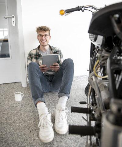 Auszubildender im E-Commerce Felix auf dem Boden sitzend mit Tablet in der Hand, neben sich eine Kaffeetasse und ein Motorrad