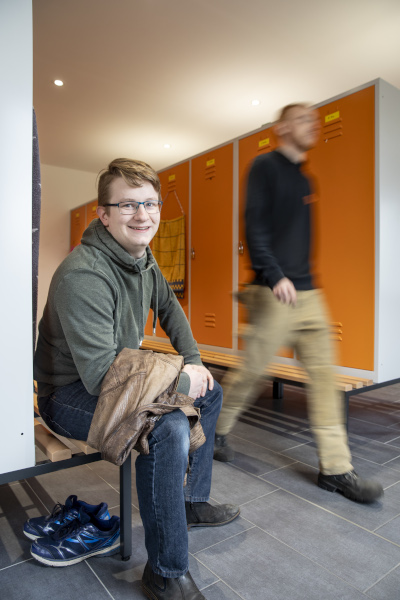 Auszubildender Robert sitzt im Umkleideraum seiner Firma vor einem Spind