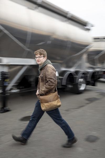 Auszubildender Robert geht an einem Tanklaster vorbei