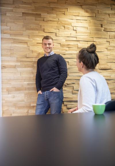 Auszubildender Immobilienkaufmann Timon lehnt an einer Wand, unterhält sich mit einer Kollegin