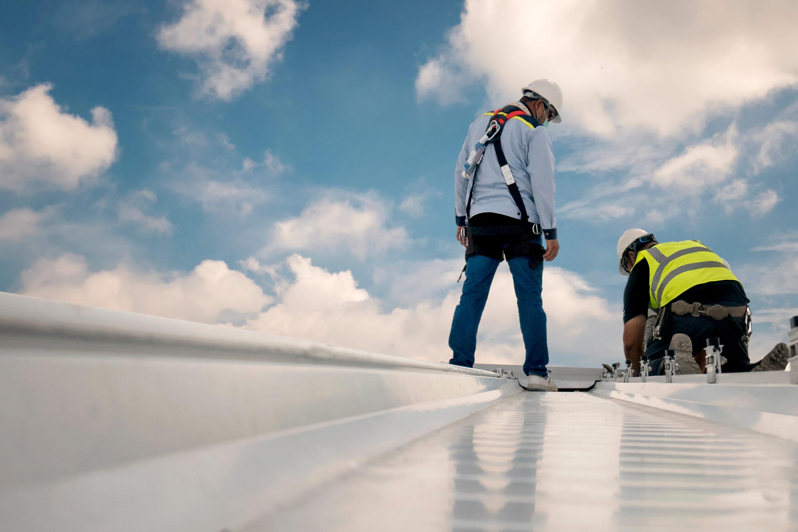 Zwei Maenner in Arbeitskleidung arbeiten auf einem Dach einer Industriehalle