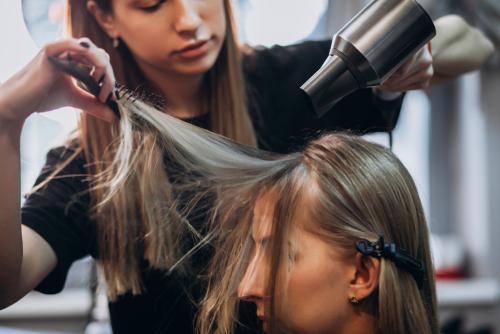 Friseurin schneidet Haare von schoenem blondem Maedchen, Foehn, Haarbuerste, Ausbildung im Handwerk, Moin Future
