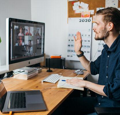 Junger Mann arbeitet von zuhause und nimmt an einer Videokonferenz teil