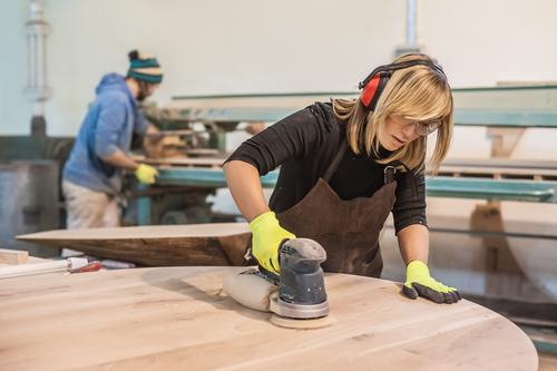 Auszubildende zur Tischlerin bearbeitet mit einem Schleifgerät einen großen, runden Tisch aus Holz