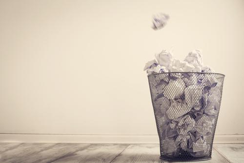 Zerknuelltes Papier fliegt in den Papierkorb