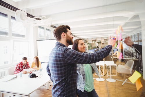 Laechelnde Geschaeftsleute, die sich im Sitzungssaal des Kreativbueros Postits auf Glas ansehen