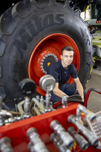 Auszubildender Lars Landmaschinen sitzt in einem Trekker-Reifen