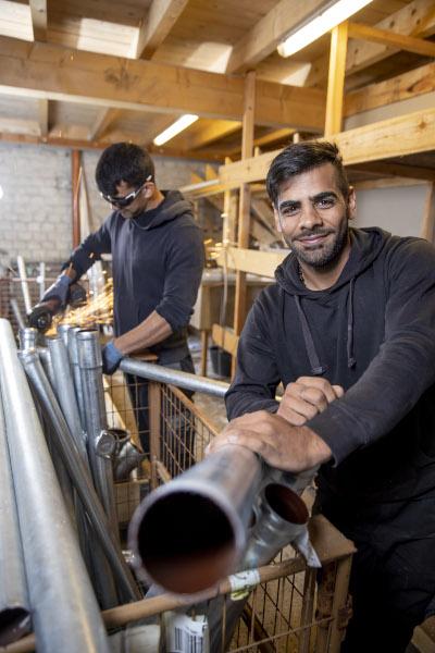 Auszubildender Ramazan Dachdecker lächelt in die Kamera in der Werkstatt